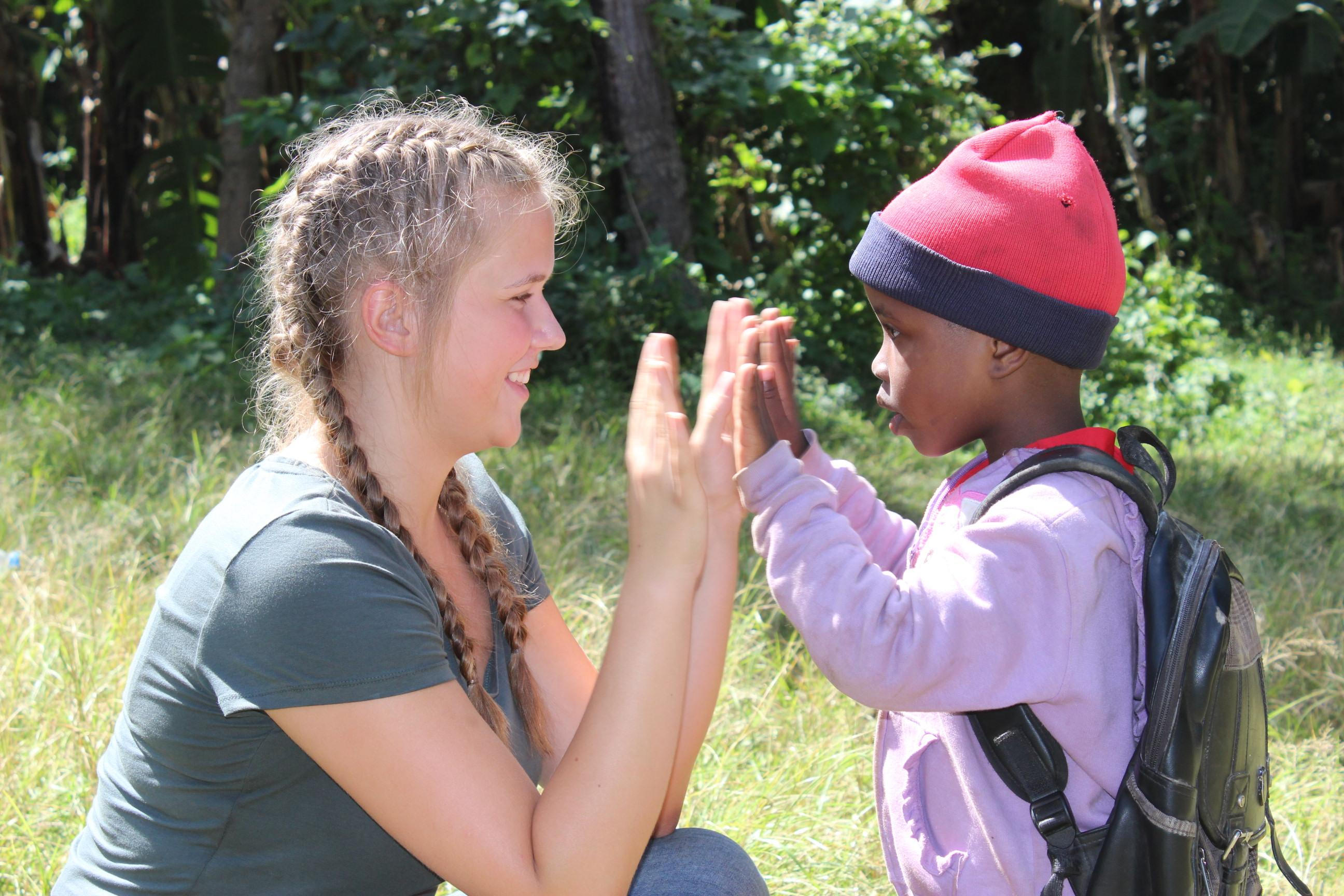 Female volunteer working with children in Tanzania high fives a young boy outside a care centre.
